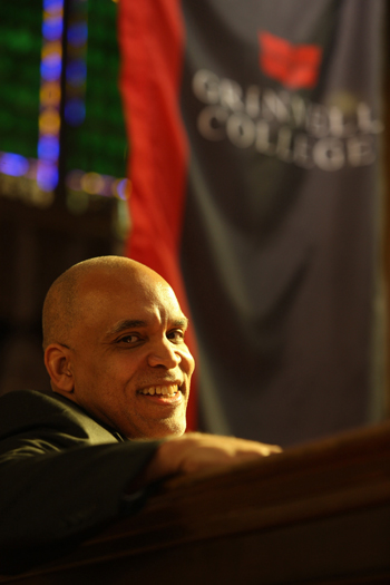 Kington smiles, turned to look over back of pew, with Grinnell College banner in the background