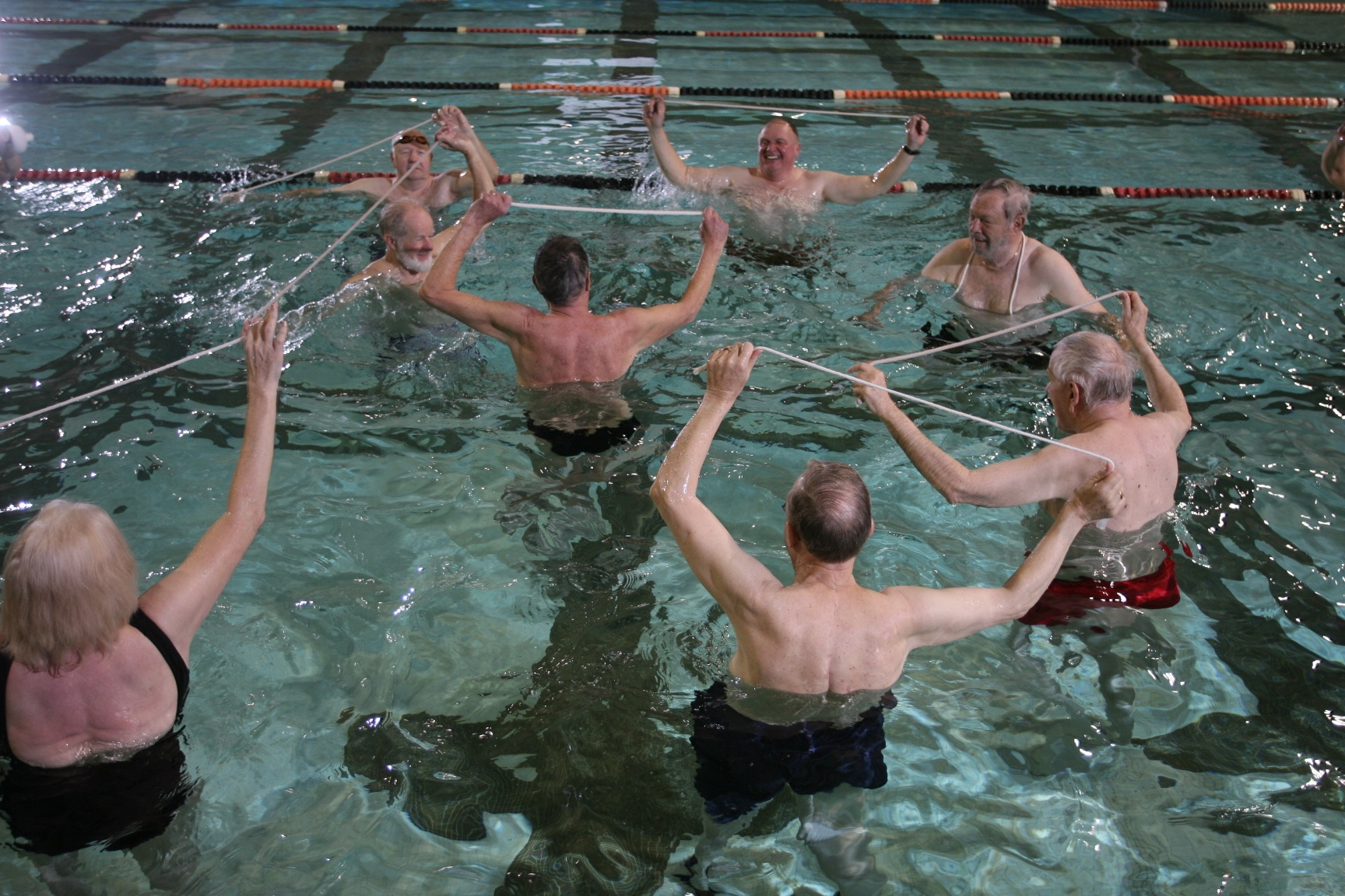 bunch of people in pool holding short pieces of rope in the air