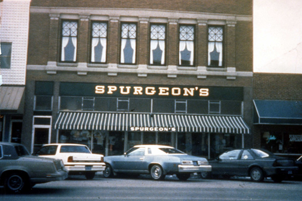 store front with striped awning, and Spurgeons on awning and above.