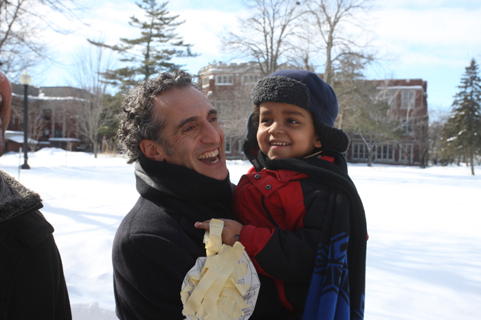 Daniolos holds Emerson, both in coats, against snowy campus. Emerson smiles as he holds construct of tape and paper.