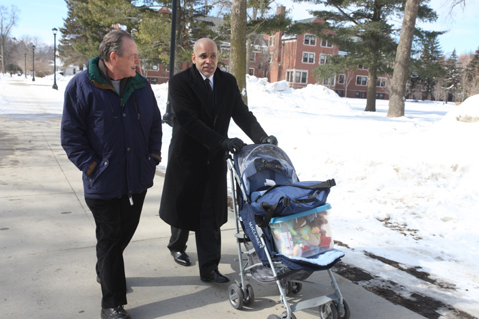 Fuson walks next to Kington, who is pushing a stroller filled with child supplies
