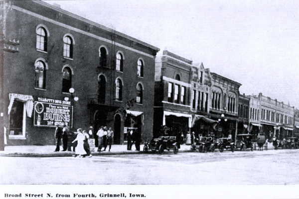 long line of cars and people walking along, drugstore with cigar advertisement on left
