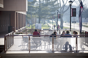 Students studying at outdoor tables.