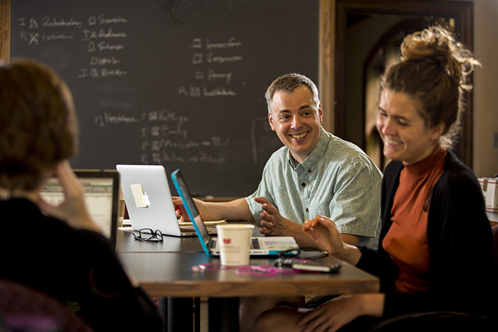 Professor and students laughing around a table with their laptops