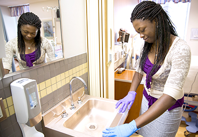 Queenster Nartey '16 testing copper surfaces for bacterial growth at a local hospital