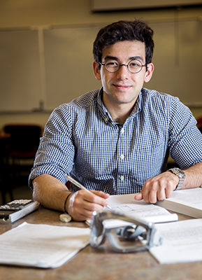 Micah Iticovici '16 working at a table with books, papers
