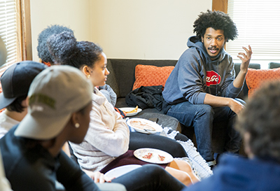 Casually dressed, Damon Williams and students talking over pizza in a casual environment