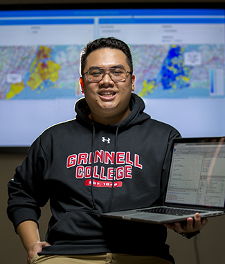 Jarren Santos holds his laptop with digital maps appearing behind him