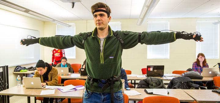 Student wearing motion-capture suit stands with arms out while classmates work in the background