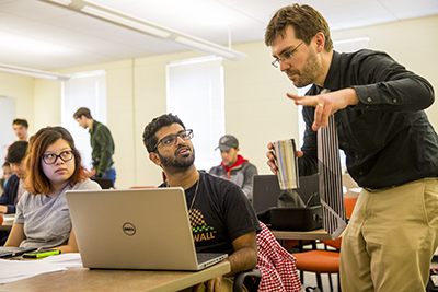 Damian Kelty-Stephen talks to two students in class working at their computers