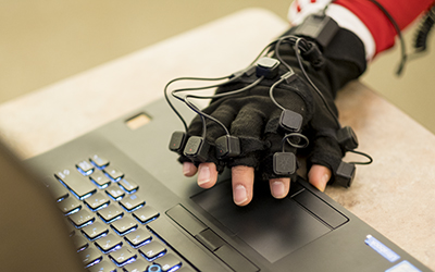 Hand in motion-capture glove hovers over the touchpad of a laptop computer
