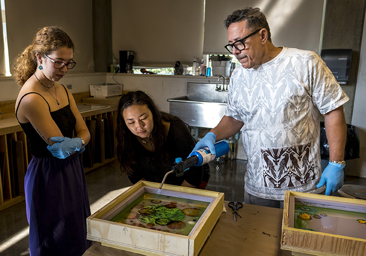 Artist and two students use a blowtorch on a resin block