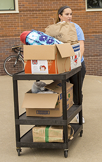 Pushing a cart full of donation items.