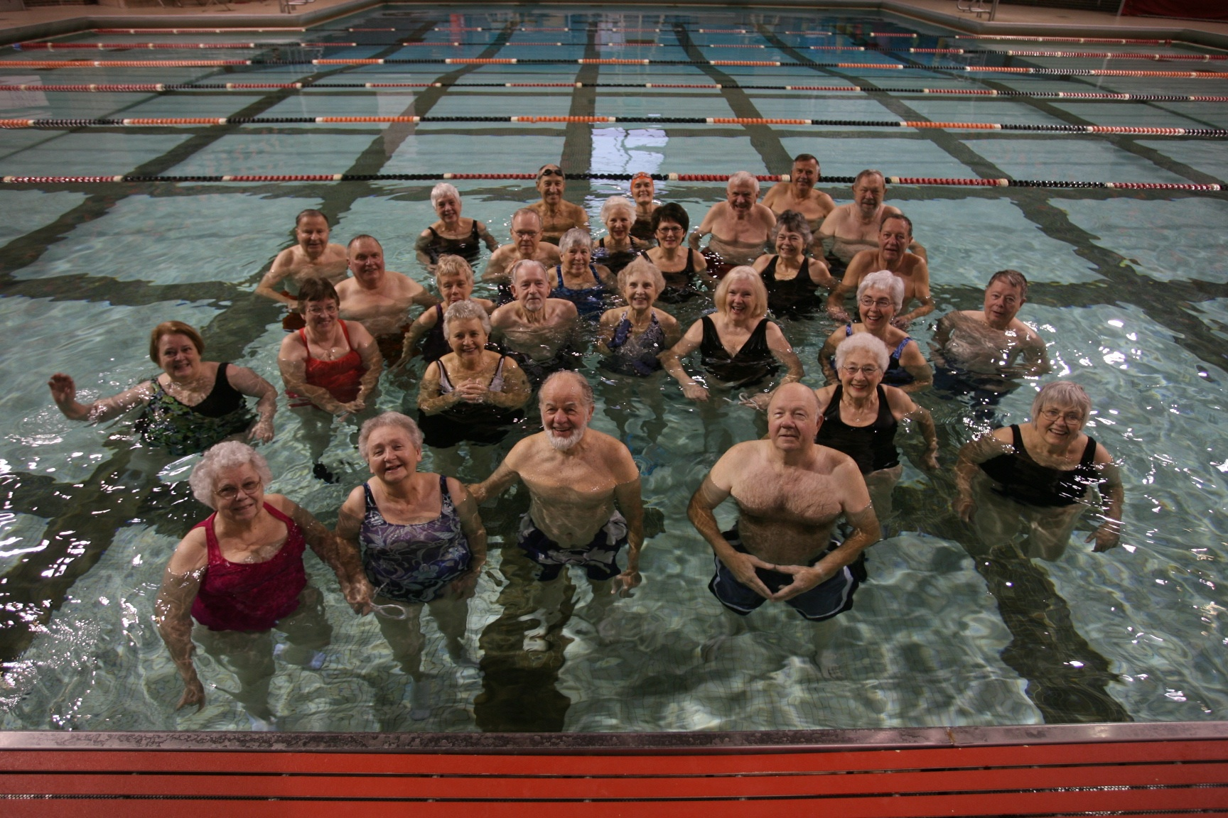men and women together for a group shot in the pool