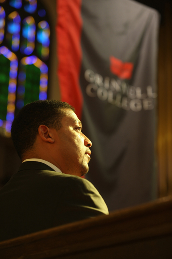 David White in pew, Grinnell College banner in background