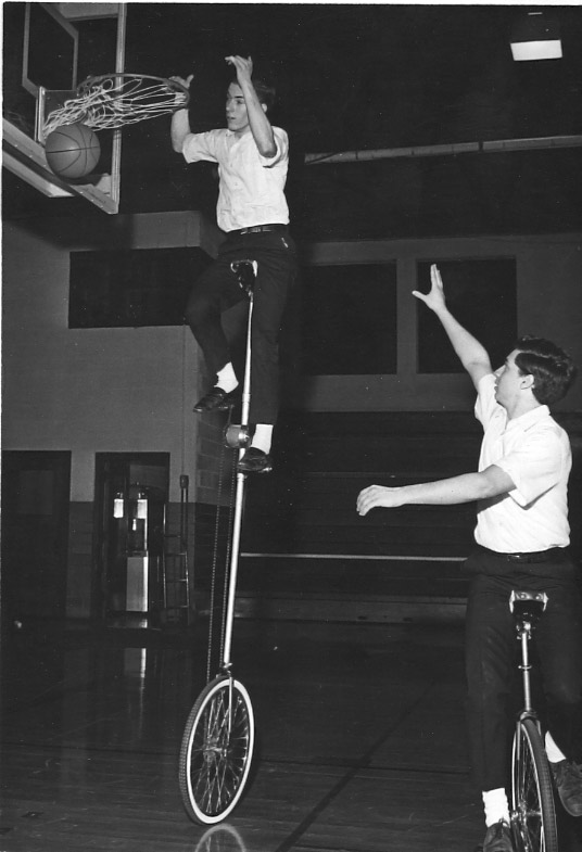 One man dunks a basketball from a unicycle that makes him about twice as tall as normal. Another man on a unicycle looks to have just passed the ball up to him