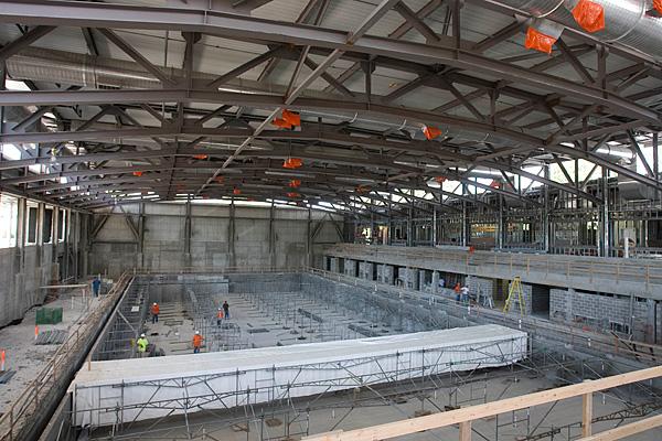 Interior of natatorium with concrete, beams, construction workers