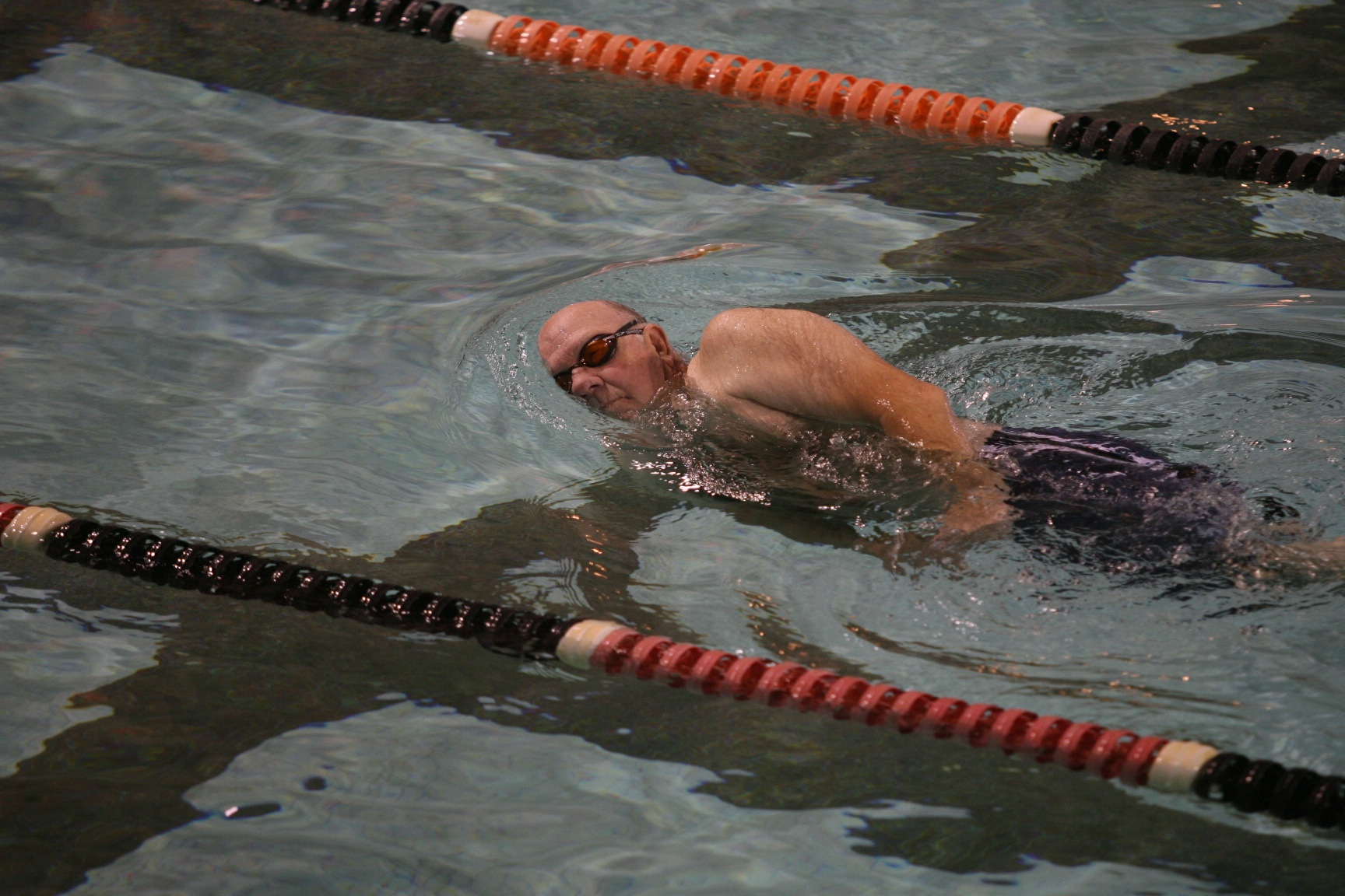 man on his side swimming laps