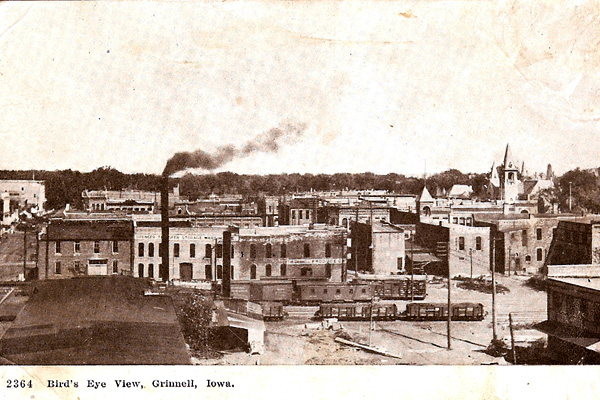 View from a high angle showing brick buildings, railroad tracks, a smoke stack, and a church in the top right corner