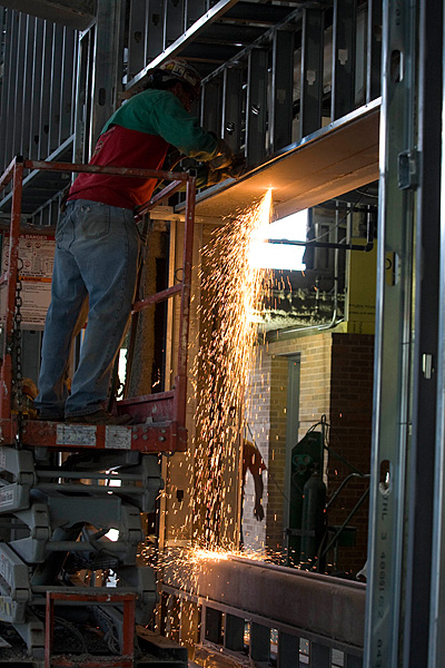 Welder leaning over a beam and sparks falling below