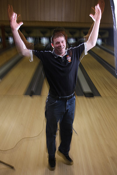 Long exposure of man jumping with hands in the air next in bowling alley