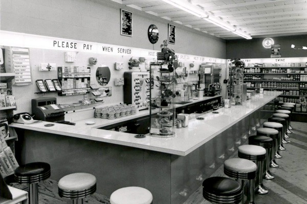 a drug store counter with fixed stools, with food and drink for sale, and a back wall with signs