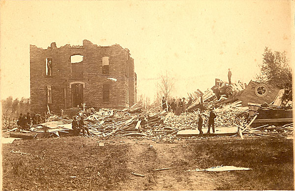 Men climbing through the rubble of two buildings one with partial wals, the other flattened