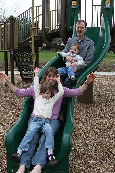 Young girl on a woman's lap go down a green slide, followed closely by a smaller child on a man's lap