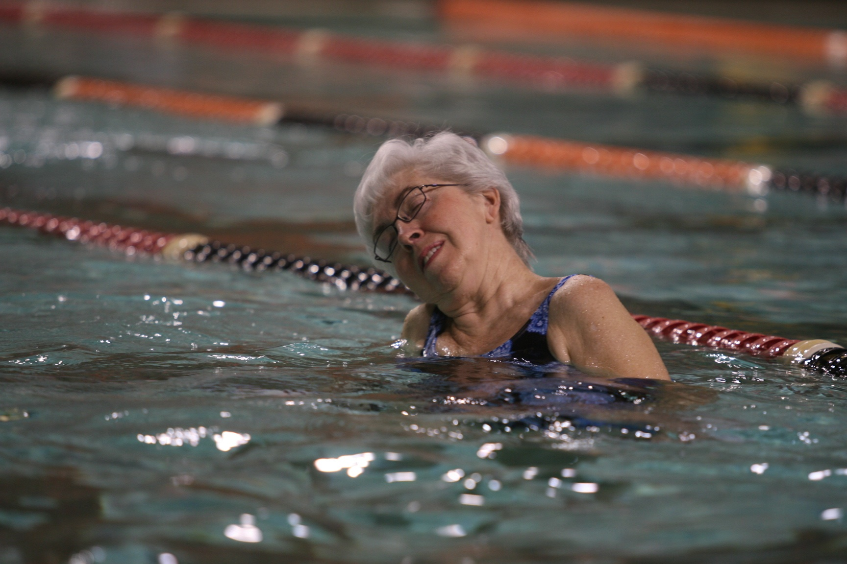 woman in pool stretches head to the right shoulder