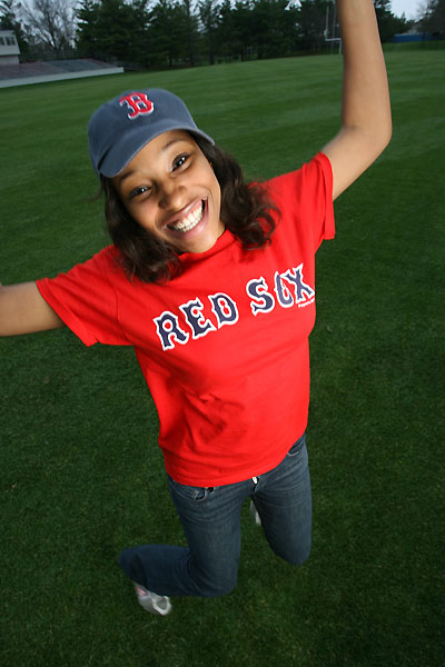 Smiling woman in a Boston Red Sox hat and tshirt jumping