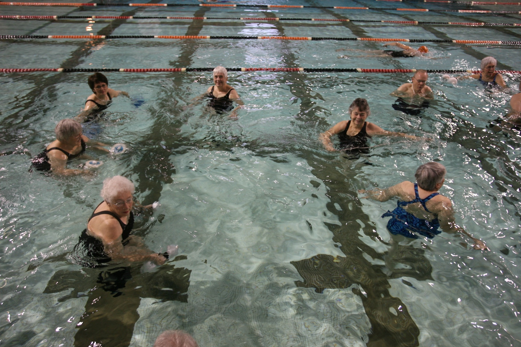 women in pool holding ropes and pool weights
