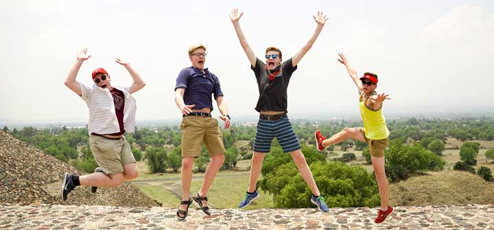 Four students ham it up in a leap on the top of the pyramid