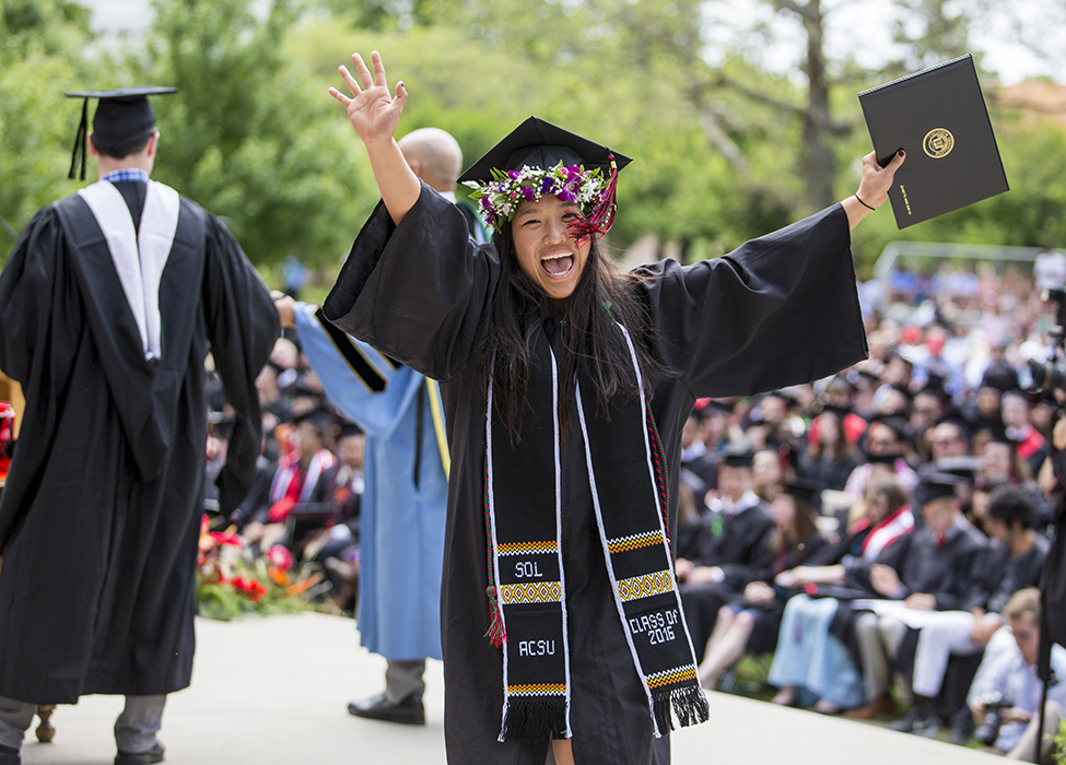 Graduate with diploma with mortarboard wreathed in flowers