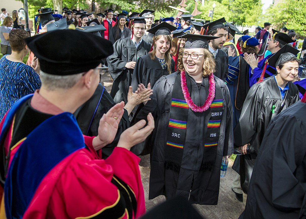 Students receive congratulations from professors lining the processional path.