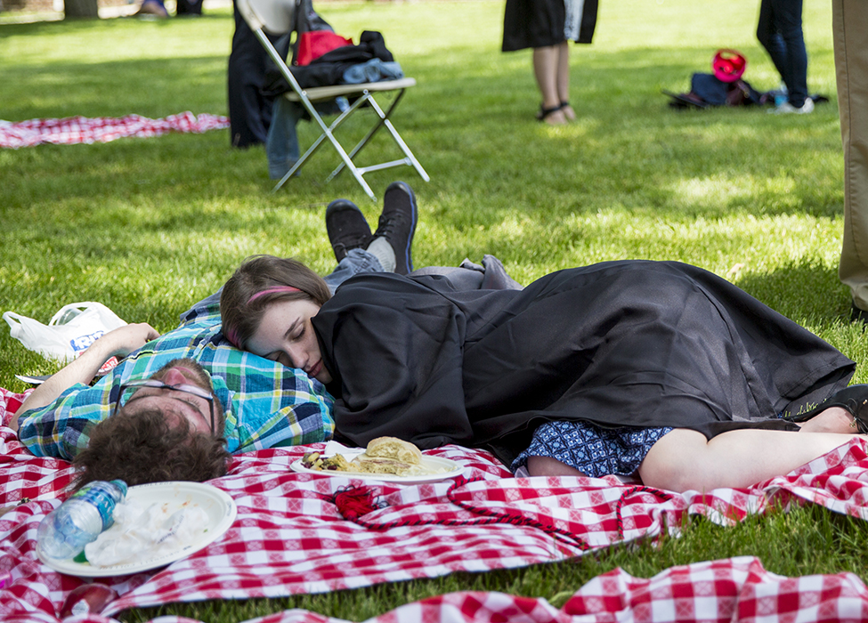 Two people napping on red and white checked picnic blanket