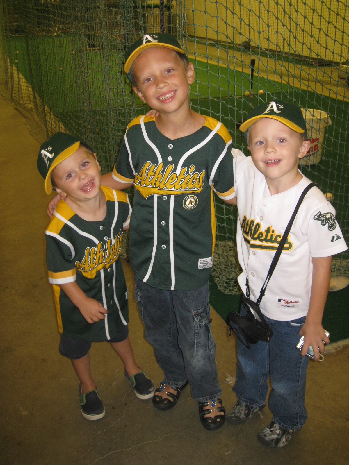 three boys in A's gear posed in front of cages