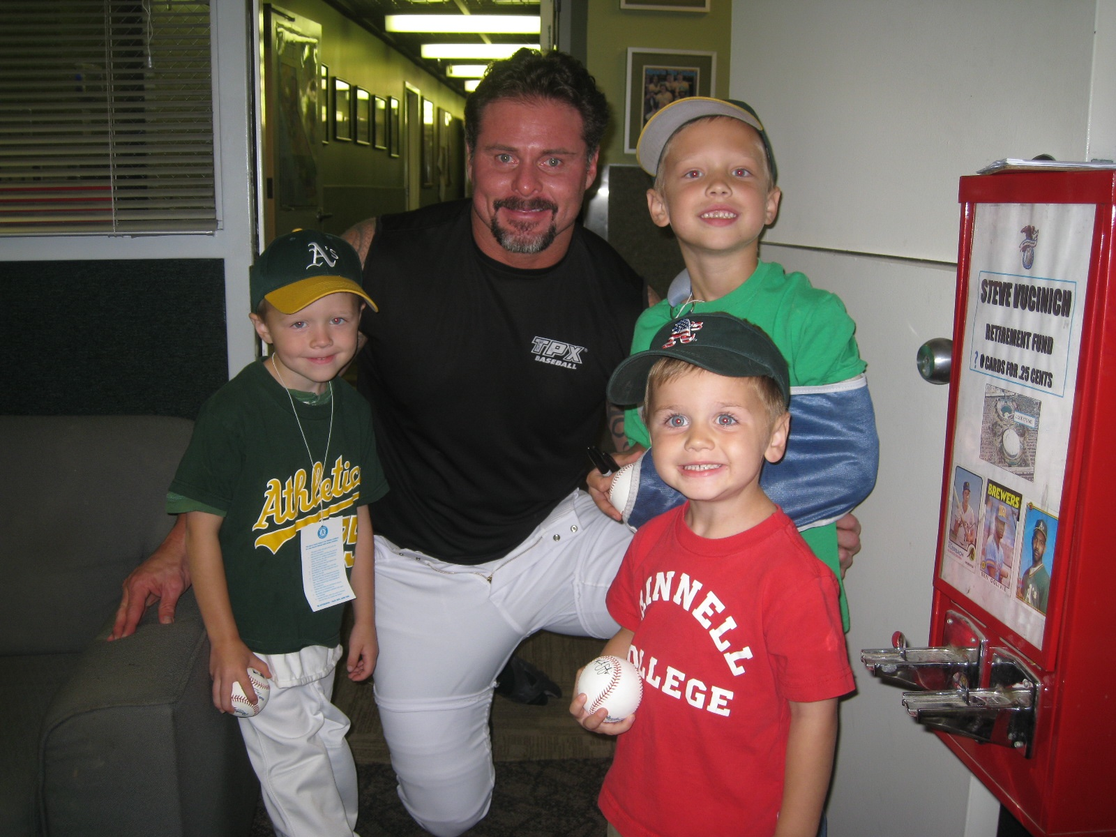 Giambi kneels between the three boys for a snapshot