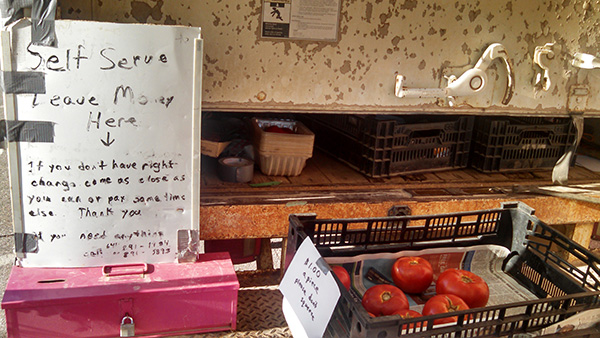 Baskets of vegetables with a sign explaining their self-service honor system