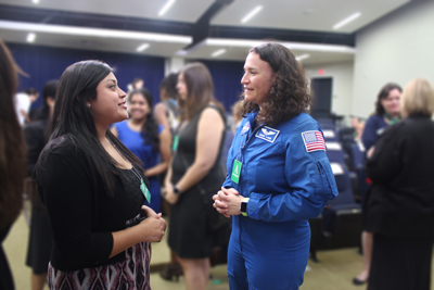 Ayala talking with Auñón (who is in a NASA suit) at a gathering