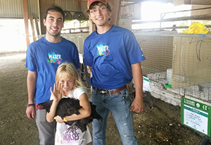 Nick Hunter with fellow intern Lance Henrichs pose with a new friend and her prize chicken.