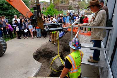 Crowd watches as John Whittaker oversees the forklift drawing the Peace Rock out of it's hole.