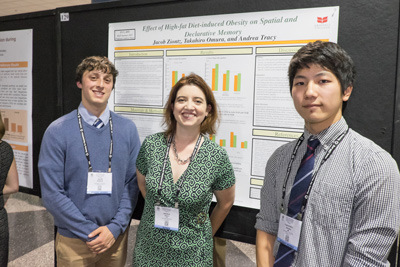 Students and professor in front of poster titled Effect of High-fat Diet-induced Obesity on Spatial and Declarative Memory
