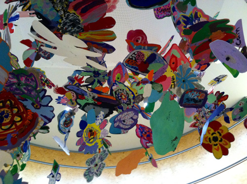 Colorful paper and paint flowers suspended from ceiling