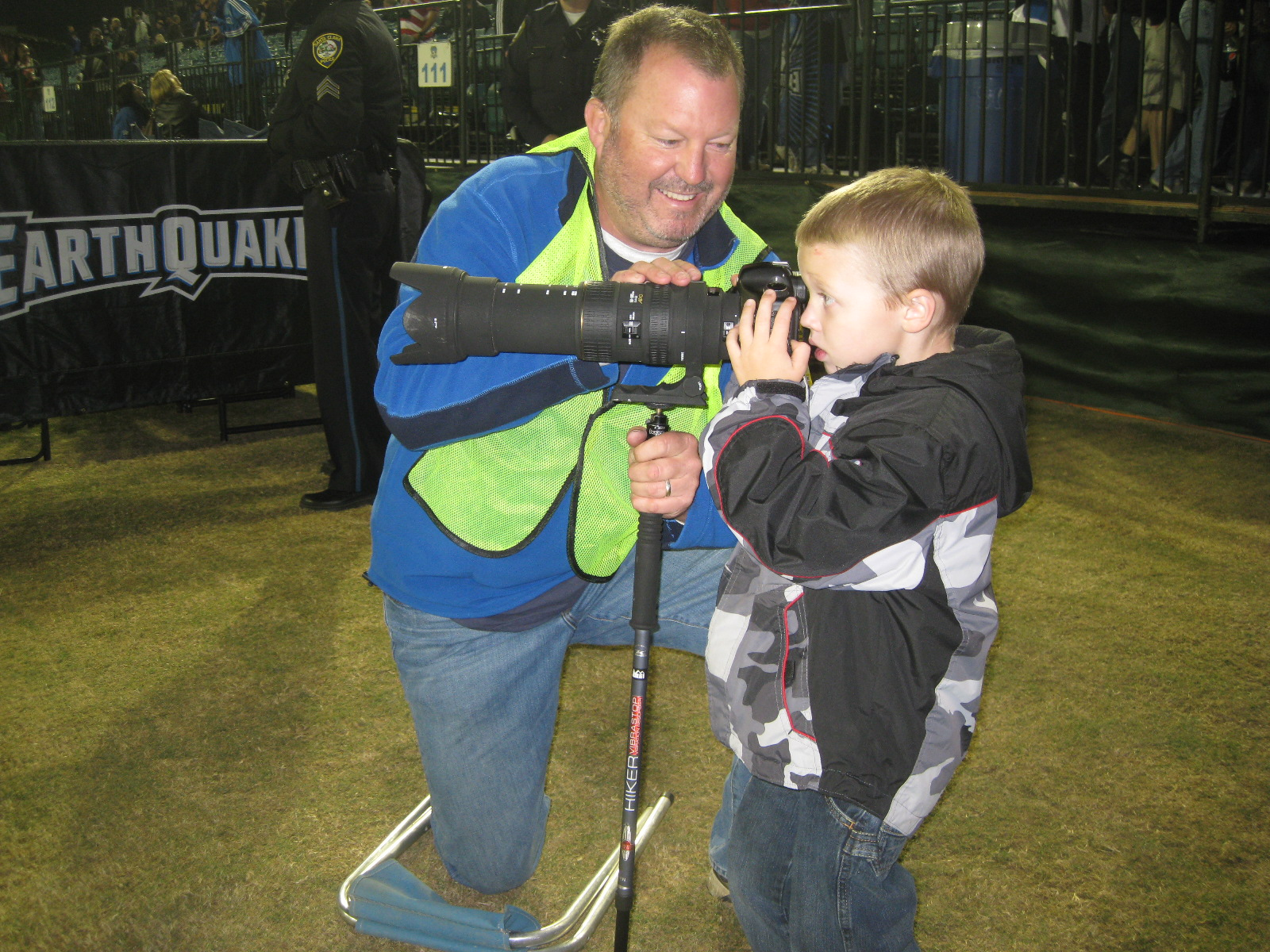Boy looking through lenses of large camera on stick as man kneeling nearby supports it