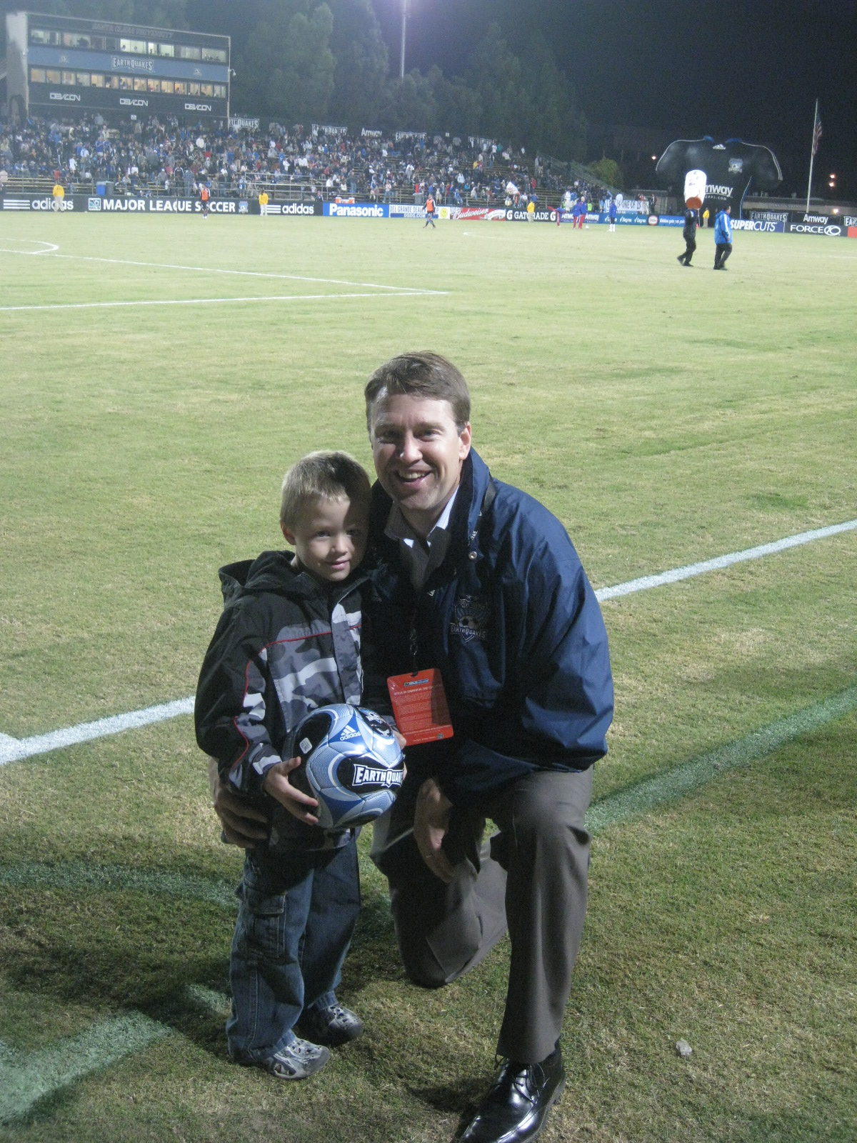 son holding soccer ball next to kneeling dad on the field