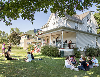 Groups of students lounge on grass, sit on porch in front of Food House