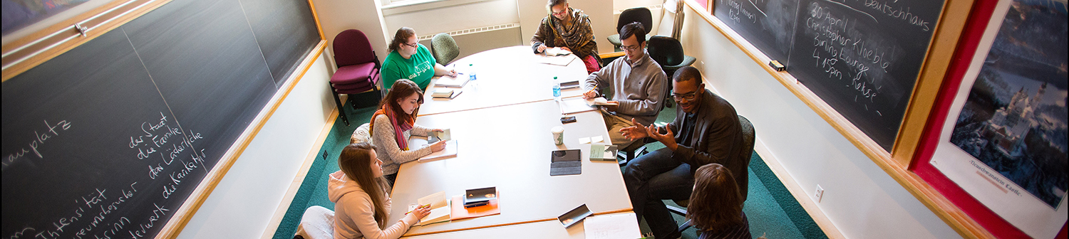 Six students and a professor sit around a classroom discussion table