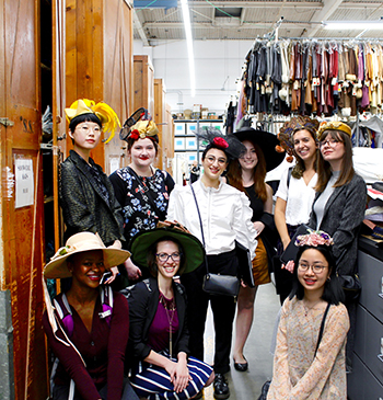 Grinnellians try on hats at Western Costume