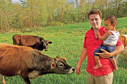 Man holding small boy standing next to cows