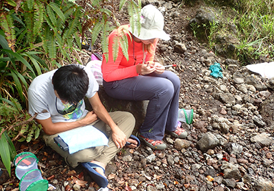 Students sitting on ground with research tools around them.